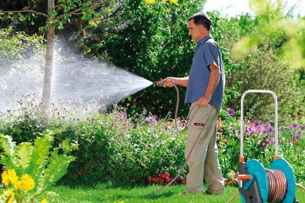 Мужчина поливает в саду